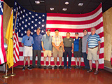 The group poses for a photo at the museum. L-R: Bob Fitzgerald, John Ging, Paul Baker, Jerry Smith, Bob Strand, Wayne Miller, Steve Bisel and Leon Skatburg